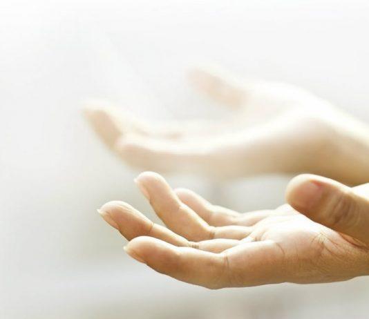 Mãos abertas viradas ao céu pedindo que Deus cure