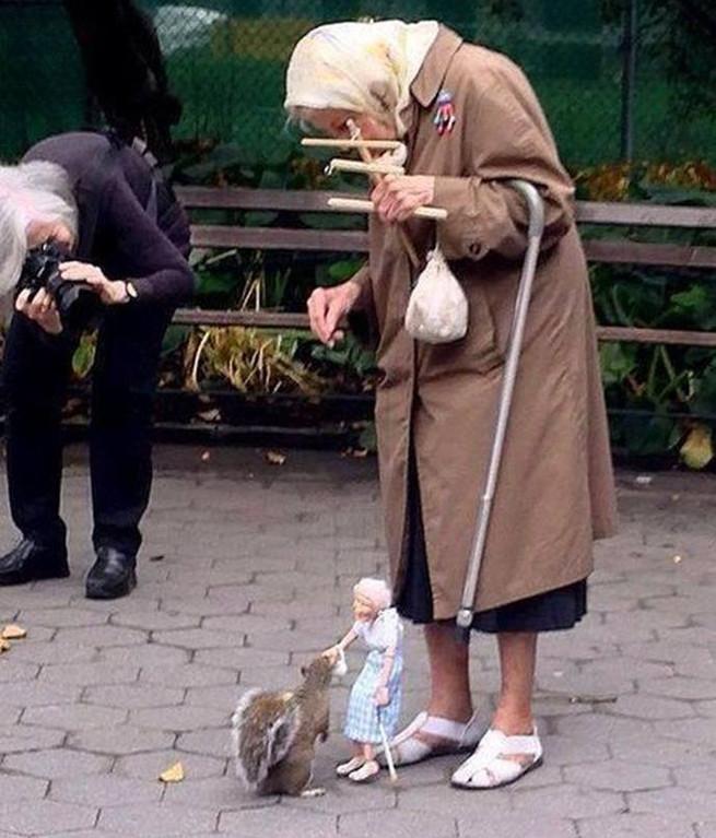 senhora-alimenta-esquilos-com-uma-marionete-de-si-mesma